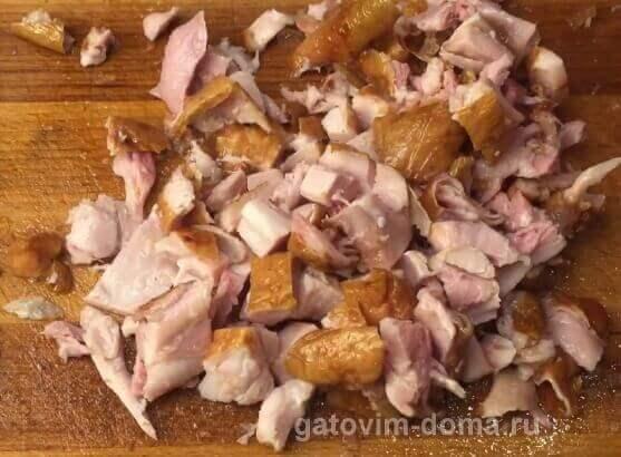 Разрезанный копченый куриный окорочок с кожицей для салата обжорка