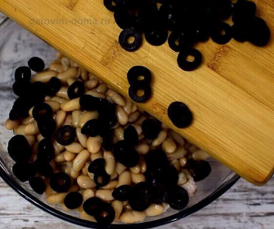 Добавляем фасоль без сока и нарезанные маслины в общий салат