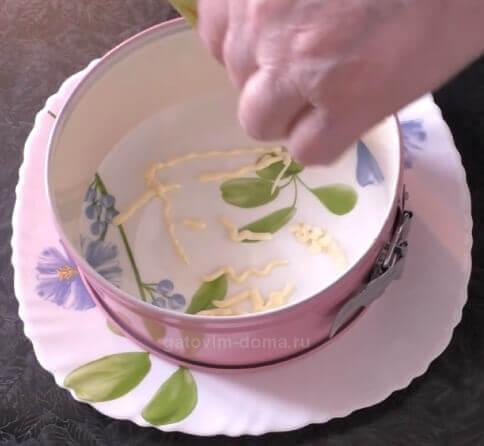 Круглая разъемная форма розового цвета на тарелке с майонезом