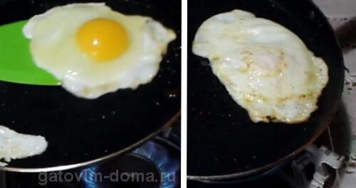 Переворачиваем жареную яичницу на другую сторону в сковороде