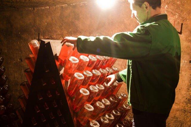 Работник переворачивает красное игристое вино